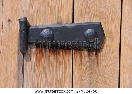 Black medieval door hinge on the wooden gate in Bulgaria  - stock photo