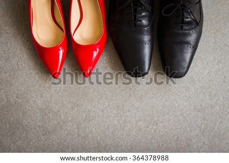 Black men shoes and red women shoes on gray background - stock photo