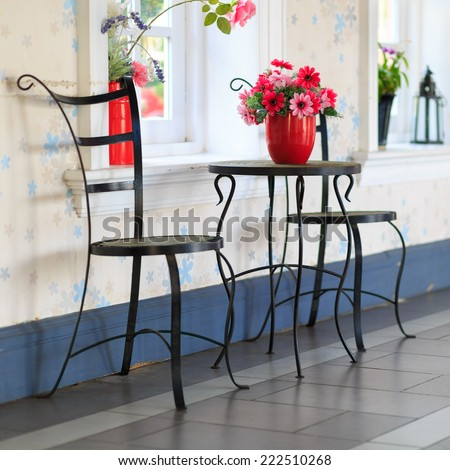 black metal chair and table with red vase flower in vintage room - stock photo
