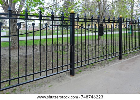 Black metal fence outdoors. Spring day