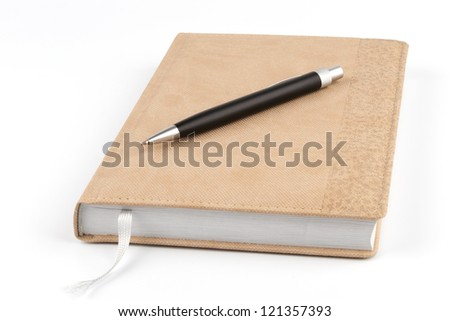 Black metal pen on diary of beige color on a white background