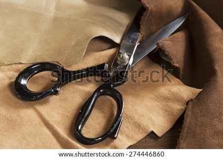 Black metal scissors on a leather - stock photo