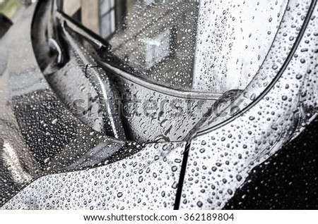 Black metallic shining car hood fragment and windshield wipers with raindrops on it, closeup photo with selective focus and shallow DOF - stock photo