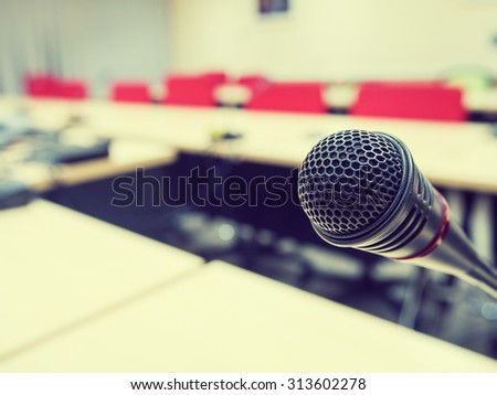 Black microphone in conference room or symposium event with de focused laptop is working in background. : Vintage style and filtered process - stock photo