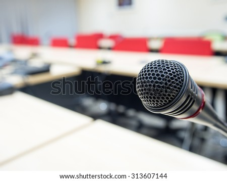 Black microphone in conference room or symposium event with de focused laptop is working in background. - stock photo