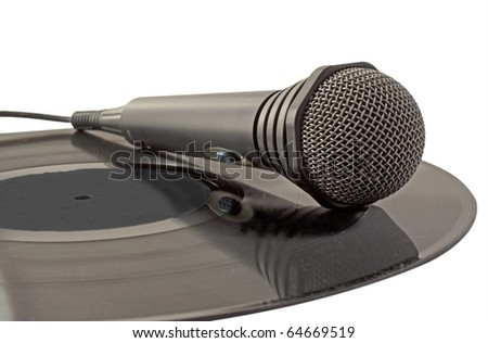 Black microphone laying over a vinyl record - stock photo