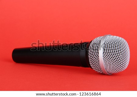 Black microphone on red background