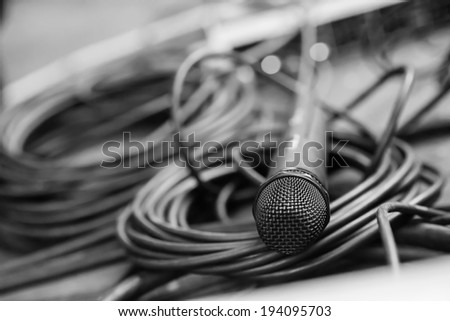 Black microphone with black wire on the floor