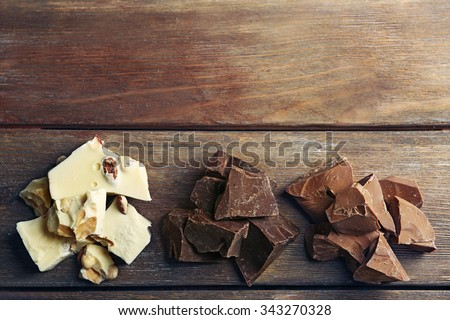 Black, milk and white chocolate pieces on color wooden background - stock photo
