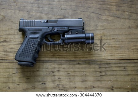 Black 9mm Pistol and Tactical Light - stock photo