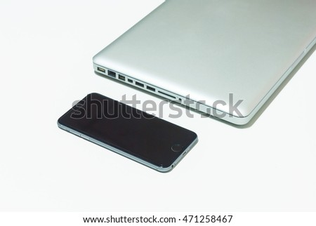 Black mobile phone and laptop on the white table.
