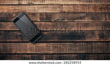 Black mobile phone on a vintage hardwood desk and blank copy space - stock photo