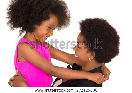 Black mother daughter posing happily and facing each other with big smiles - stock photo