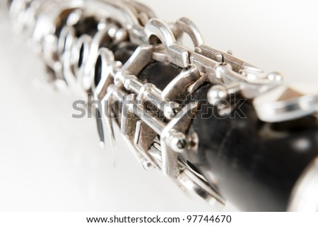 black music clarinet decorated with silver metal on white background - stock photo