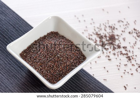 Black mustard seeds, on white bowl