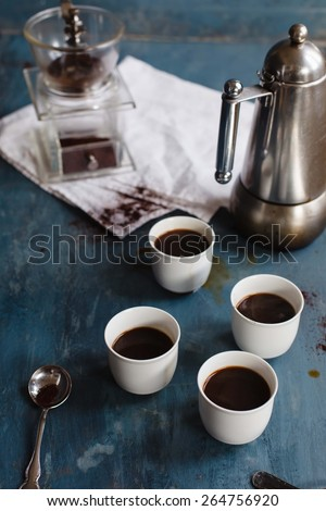 Black natural Coffee on white cups with coffeemaker taken on a blue vintage table. Rustic style. Low key.