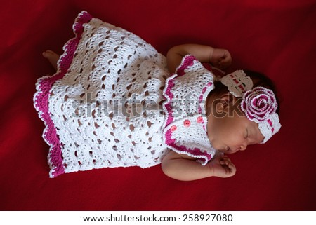 Black newborn baby in white knitted dress sleeping on a black background. - stock photo