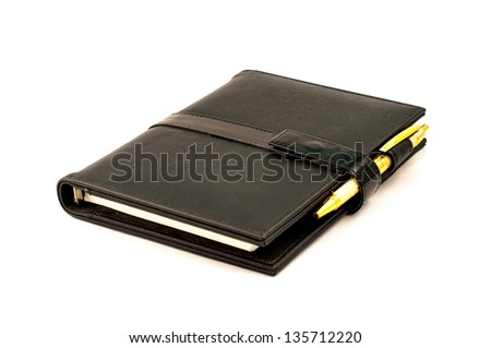 Black note book with ballpoint pen on white background