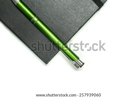 Black notebook and pen isolated on white background. - stock photo