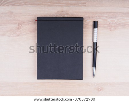 black notebook with a pen on a wooden background - stock photo