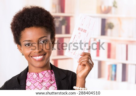Black office woman holding ticket next to her head and smiling concept transport airplane airline bus train traveling airport counter depart flight - stock photo
