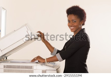 Black office woman paper in copy machine and holding lid up - stock photo
