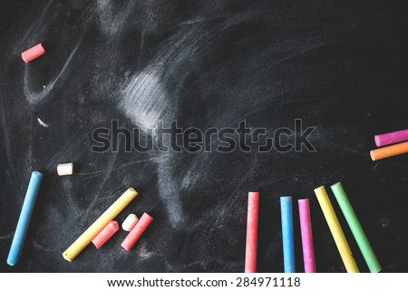 Black old empty chalkboard for copy space with colorful pieces of chalk. - stock photo