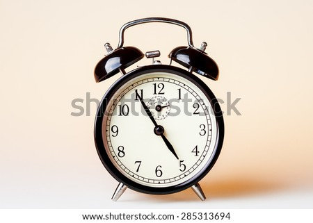 Black old fashioned alarm clock on beige background.