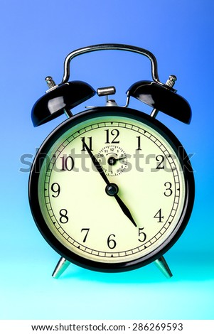 Black old fashioned alarm clock on blue background.