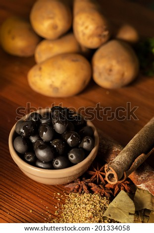 black olive (oliu )and other pizza raw materials on a wooden table - stock photo