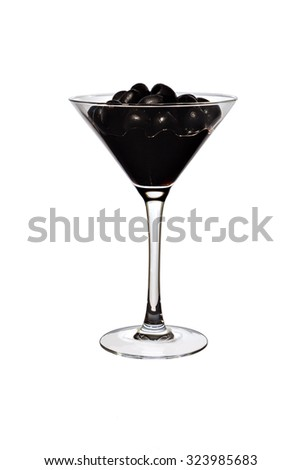Black olives and juice in a transparent glass close-up.  Black olives and juice in a transparent tall glass close-up. Full glass of juicy black olives in juice on a white background.