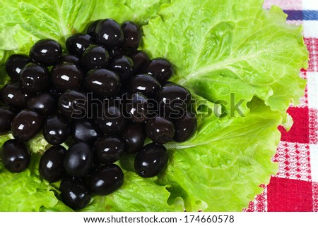 Black olives and lettuce close-up. - stock photo