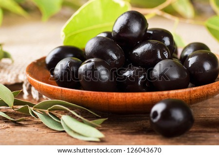 Black olives in a wooden plate and a rough board - stock photo