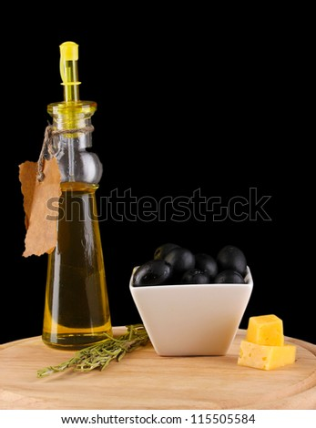 Black olives in white bowl with rosemary,olive oil and cheese on board isolated on black - stock photo