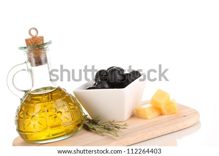 Black olives in white bowl with rosemary,olive oil and cheese on board isolated on white