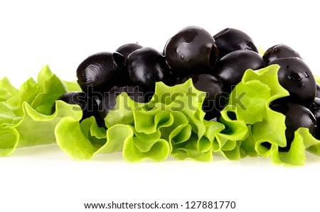 Black olives on green salad - stock photo