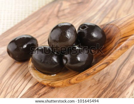 Black olives on wooden spoon - stock photo