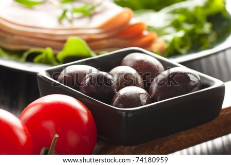 Black olives with cherry tomatoes and cold plate