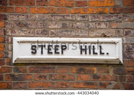 """Black on white old street name plate """"Steep Hill"""", Lincoln,England on a wall of old weathered bricks - stock photo"""