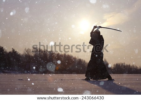 Black oriental martial arts warrior winter training - stock photo