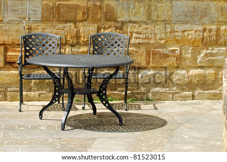 black outdoor patio set with rock wall - stock photo