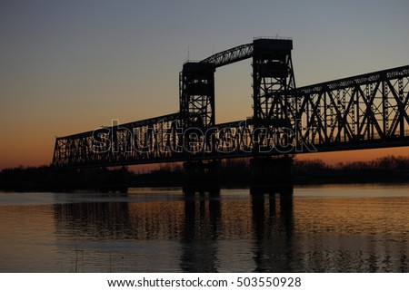 black outline of the bridge over the Northern Dvina River on the background of sunset