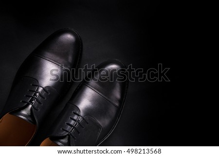 Black oxford shoes on black background. Top view. Copy space.