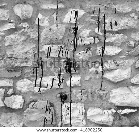 Black paint spilled on rock wall - stock photo
