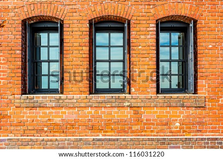 Black painted wood arched window in a red brick wall. - stock photo