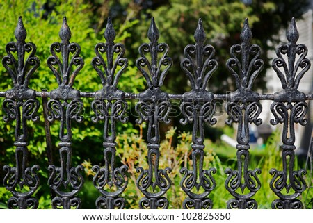 Black painted worn and weathered victorian iron fence - stock photo