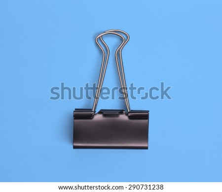 Black paper clip view from above on colored background - stock photo