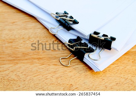 black paper clips are clipping on three set of paper in dry paint - stock photo