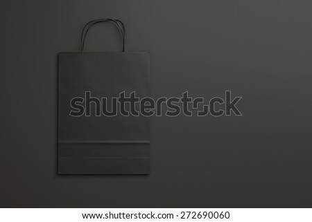 black paper shopping bag on black background with handles. 3d render - stock photo