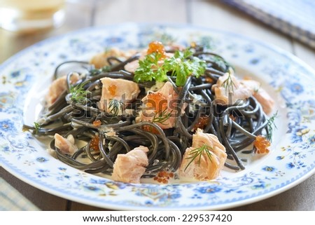 Black pasta with salmon and red caviar in cream sauce, italian cuisine - stock photo